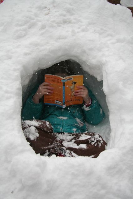 Child reading in the snow